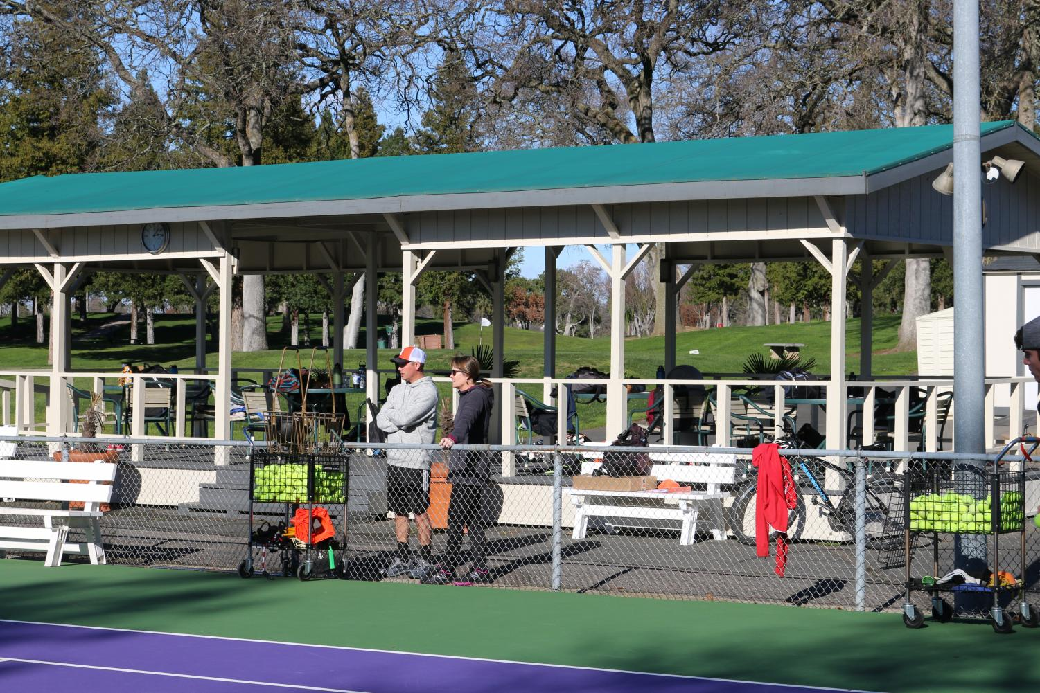New tennis coaches Michael Cerecedes and Teri Lacey recently took over RHS's varsity tennis team, both now coaching their sons on the team.