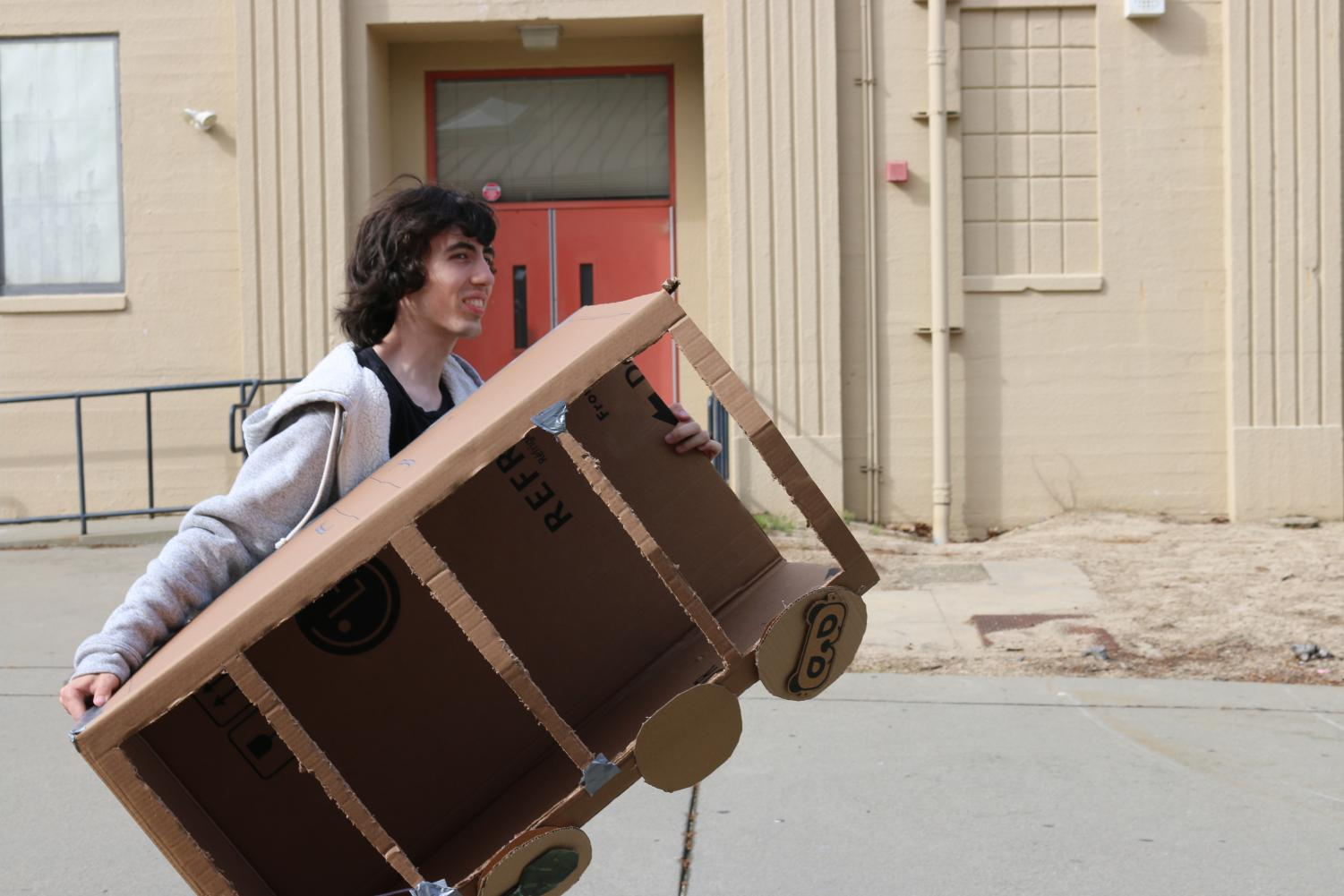 Junior Ike Bischof carries in a cardboard box to use in his self-written musical.