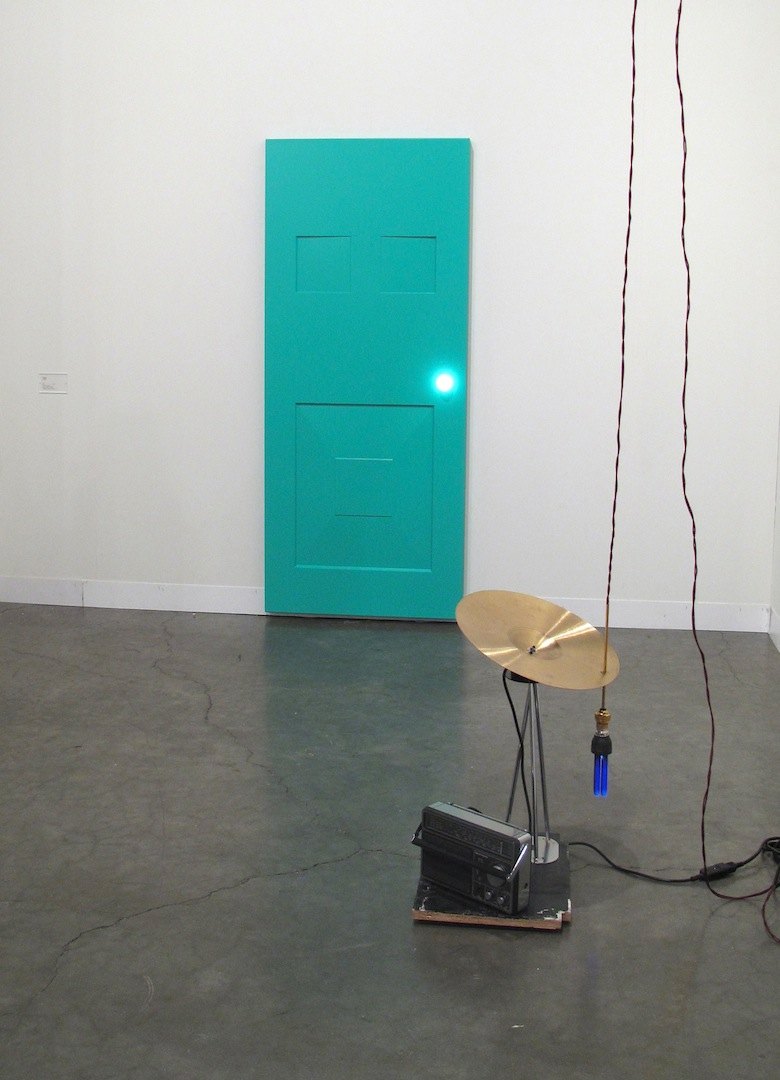 Haroon Mirza, Siren (foreground), 2012, 22 x 15.7 x 13.8 inches, Cymbal, motor, wood, table leg, UV light bulb, light fixture, fabric cable, radio      He Xiangyu, I'm Sorry (background), 2013, Stainless steel, pain, wire, lamp