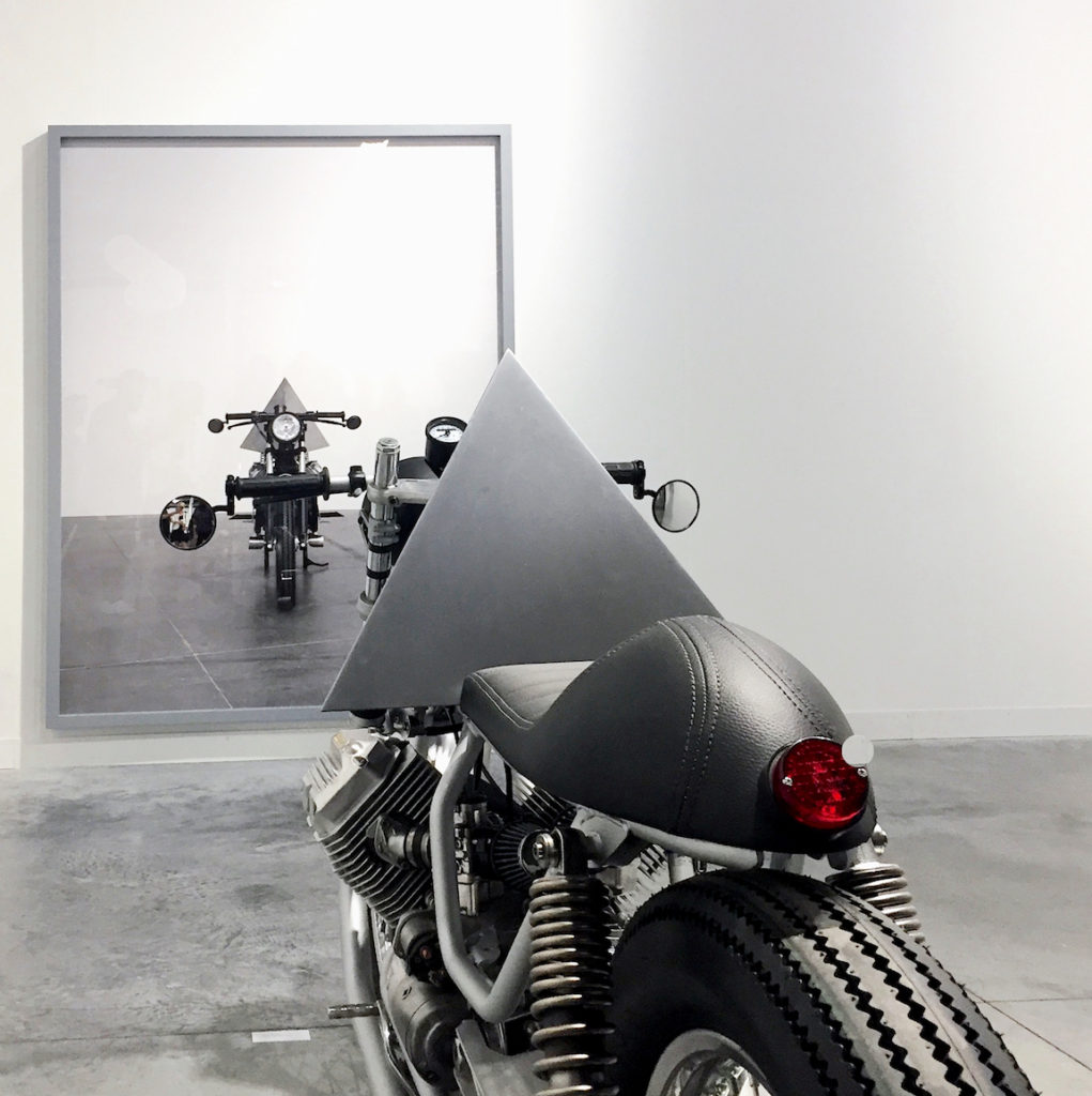 "Andrea Galvani, Installation view from ""A Few Invisible Sculptures"" (detail, photograph in background/ custom motorcycle in foreground), Revolver Galerie, Peru, Art Basel Miami Beach, Photograph by Katy Hamer, 2016"