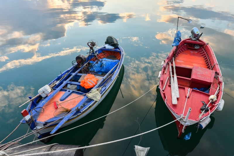 Alfonso Di Vincenzo Two small wooden fishing boats in the port of Corigliano Calabro, Calabria, Southern Italy, under the sky at sunset reflected in the calm waters of the sea.