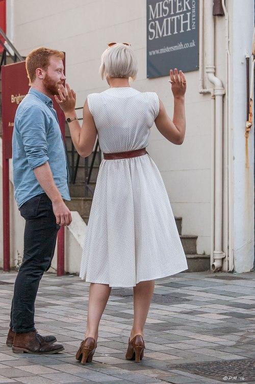 Young man talks to young woman in white polkadot dress, Brighton UK 2014 eyeteeth.net