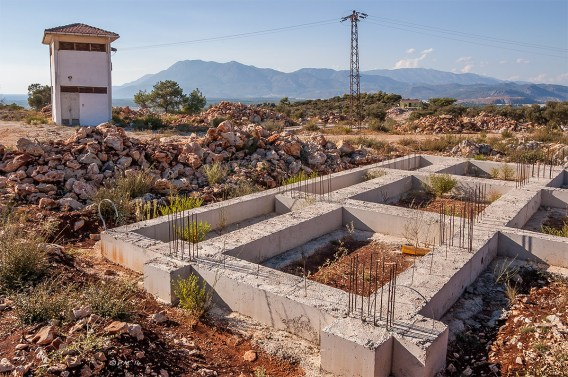 Abandoned foundations among rocks with electrical building and mountains in background. Patara Turkey. Landscape Colour. P.Maton 2014 eyeteeth.net