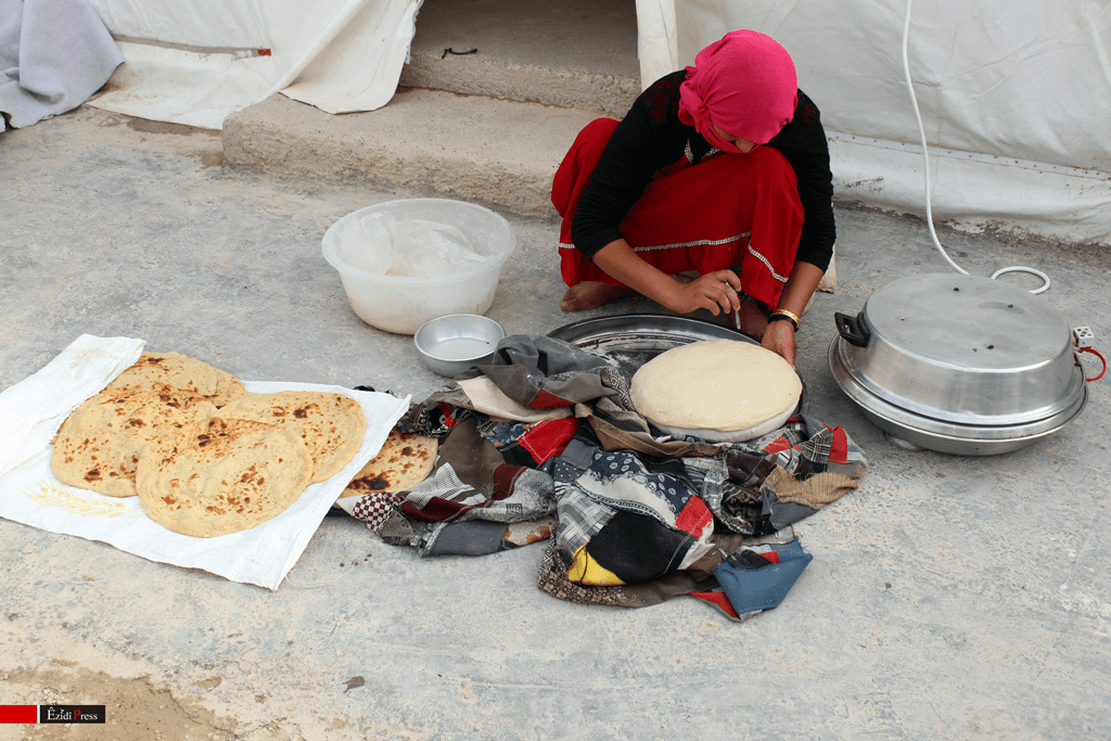 An Yezidi mother bakes bread in front of her tent in the refugee camp of Sharya