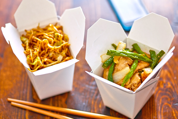 chinese take out in boxes with chopsticks and phone in backgroun