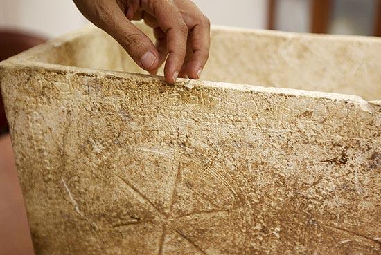 Funcionário da Autoridade Israelense de Antiguidades mostra inscrição em ossuário