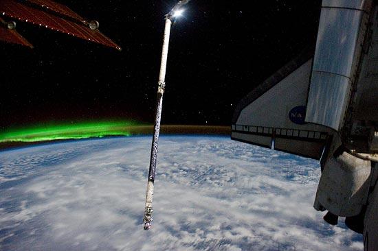 Luz verde da aurora austral pode ser vista à esquerda do Atlantis