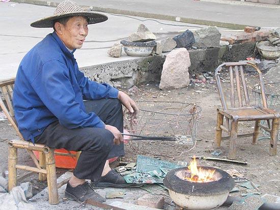 China e Índia estão entre os principais receptores de lixo eletrônico; homem queima placa para remover metais
