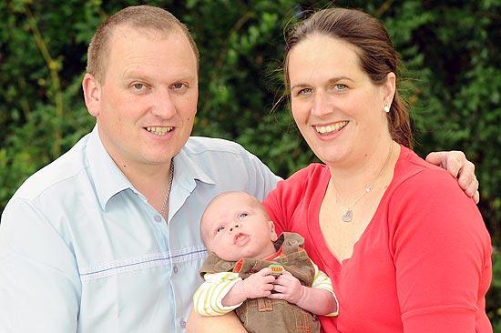 O casal britânico Nicky e Neil Halford segura o filho Tom, que nasceu saudável após passar por um tratamento de seleção de embriões