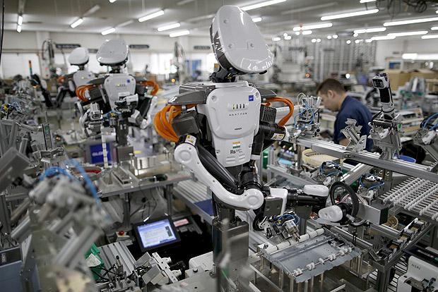 Robôs trabalham ao lado de pessoas em linha de produção em fábrica em Kazo, no Japão