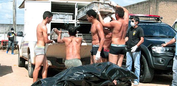 Presos carregam os corpos de detentos mortos em massacre na penitenciária de Monte Cristo, em Boa Vista