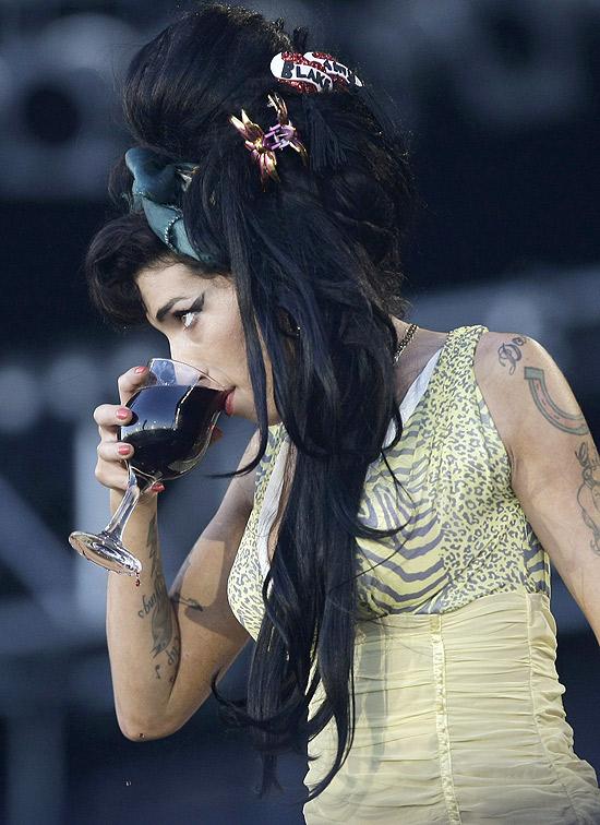 Amy Winehouse bebe uma taça de vinho durante sua performance no festival Rock in Rio Madri