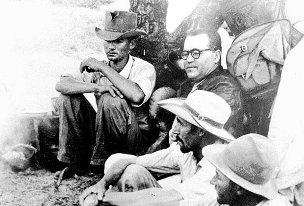 """ORG XMIT: 390901_0.tif O escritor João Guimarães Rosa (de óculos) e sertanejos em maio de 1952. Guimarães Rosa viaja entre Cordisburgo e Três Marias, no sertão mineiro, colhendo material para o livro """"Grande Sertão: Veredas"""", acompanhado por Álvares da Silva e Eugênio Silva, repórter e fotógrafo, respectivamente, da revista """"O Cruzeiro"""" que publicou, na edição de 21 de junho de 1952, a reportagem sobre a viagem. (Minas Gerais, maio de 1952. Foto de Eugênio Silva/O Cruzeiro)"""