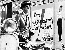 """Cena do filme """"Acossado"""", de Godard; ao fundo se lê: """"viver perigosamente...até o fim"""""""