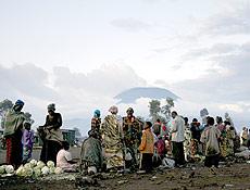 XSM011 KIBATI (R.D. CONGO), 13/11/2008.- Un grupo de personas intenta hacerse con algo de comida en un improvisado mercado en el campo de desplazados internos de Kibati en la República Democrática del Congo hoy, jueves 13 de noviembre. Al fondo se ve el volcán de Nyiragongo. Tropas de Angola y Zimbabue están ayudando al ejército leal al gobierno en su batalla contra los rebeldes en el este de la R. D. del Congo, según noticias publicadas hoy. EFE/Stephen Morrison.