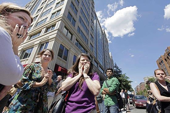Funcionários se reúnem na calçada após descer assustados do prédio em que trabalhavam, em Washington