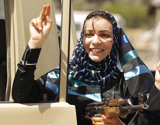 Líbia carrega um Kalashnikov do lado de fora do palácio Bab al-Aziziya enquanto o símbolo de vítória
