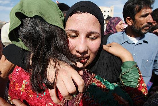 Uma prisioneira palestina é recebida por uma mulher enquanto multidão aguarda centenas de presos