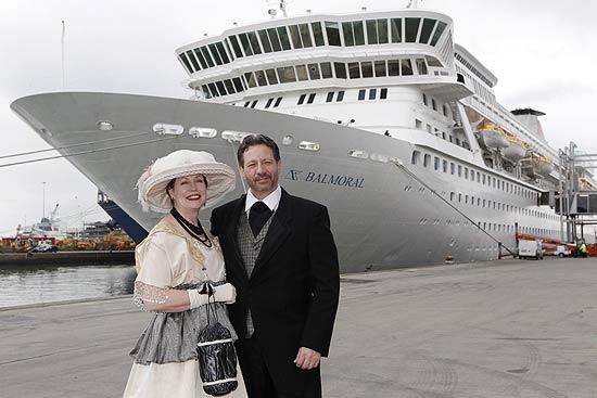 Vestindo trajes de época, casal posa em frente ao navio do Titanic Memorial Cruise, que saiu de Southampton