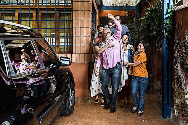 Genoino deixa sua casa para se apresentar a PF erguendo os punhos, com toalha sobre os ombros e ao lado de familiares