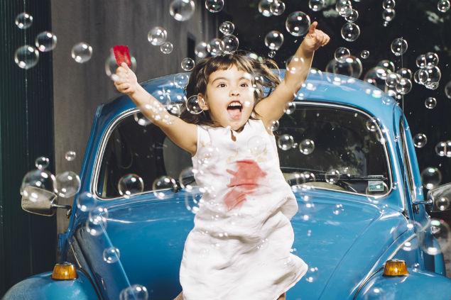Kibon, Omo e Volkswagen: campeãs nos 25 anos da Folha Top of Mind. Jade Sugino, 4, brinca em cima de carro com sorvete e bolinhas de sabão