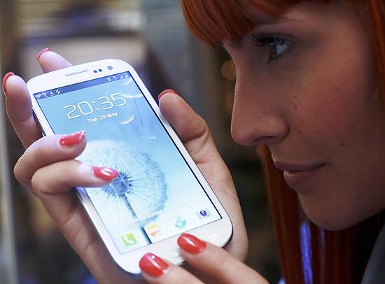 Vendedora posa com o celular Samsung Galaxy S 3, mais vendido no mundo durante o terceiro trimestre do ano