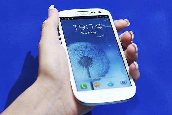 Mulher segura um Galaxy S 3 depois do lançamento do smartphone em Londres