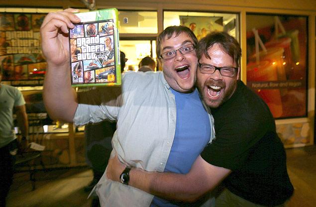 """O jogador Casey Riffel segura sua cópia do recente """"GTA 5"""" enquanto abraça o animador Michael Petterson"""