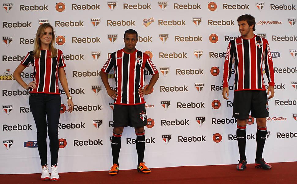 O atacante Lucas posa com o novo uniforme ao lado de modelo e do zagueiro Bruno Uvini