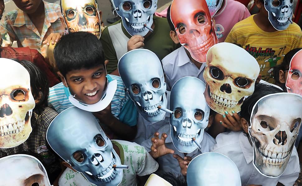 Crianças usam máscaras antitabaco em Calcutá, na Índia, durante o Dia Mundial sem Tabaco Leia Mais