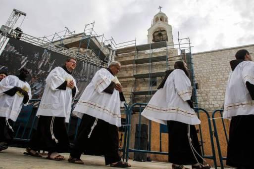 Diáconos e clérigos fazem procissão antes da noite de Natal na Basílica da Natividade, em Belém