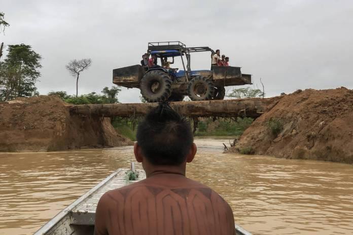 Guerreiro mundurucu, em um barco, observa jerico, trator adaptado para carga, em garimpo ilegal dentro de sua terra indígena, no sudoeste do Pará.