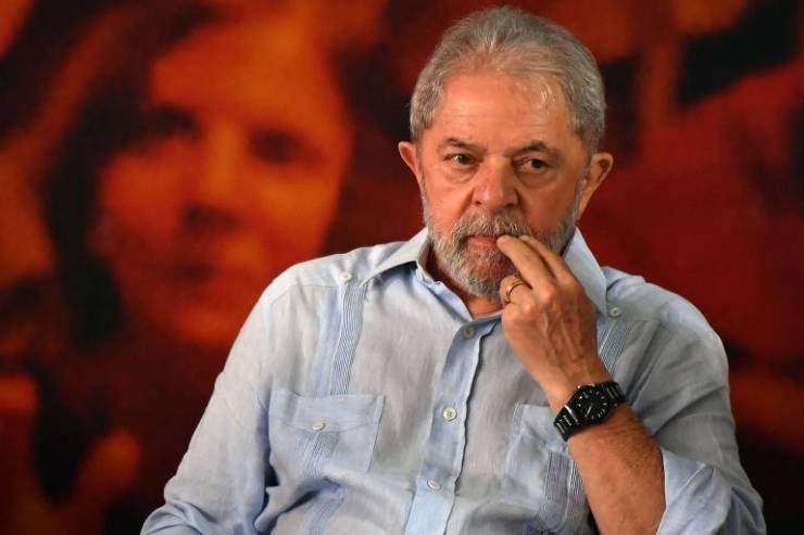 Lula sentado de camisa azul diante de painel vermelho
