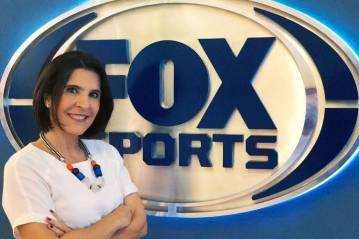 A jornalista Vanessa Riche, de blusa branca e braços cruzados, em frente ao logo do canal Fox Sports