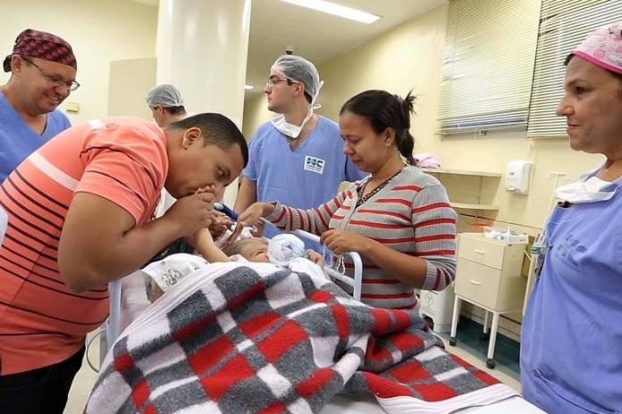 Na foto, Diego Freitas Faria e Débora Freitas Santos, pais das meninas Ysadora e Ysabelle se despedem das filhas pouco antes do início da primeira de 4 cirurgias, que permitirão que as meninas possam viver separadas