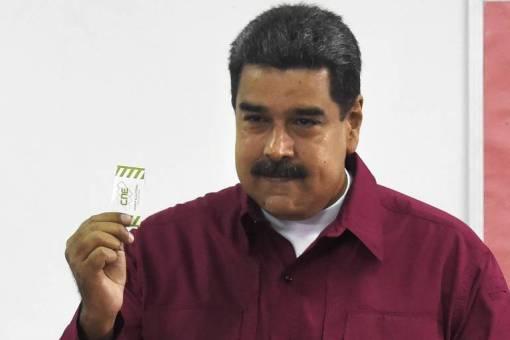 Maduro aparece de camisa vinho e camiseta branca por baixo, levantando a mão esquerda com um papel entre os dedos; ao fundo, uma parede branca