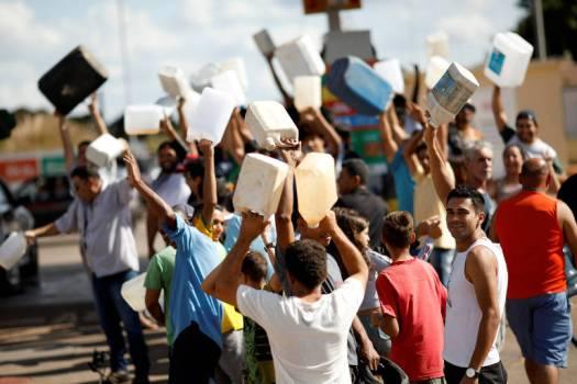 Pessoas carregam galões vazios de gasolina em frente a posto em Brasília , na sexta-feira (25)