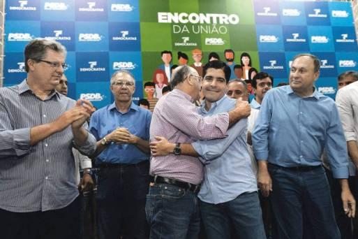 À esquerda, o tucano Jutahy Junior observa o pré-candidato do DEM ao governo baiano, José Ronaldo, abraçar o prefeito de Salvador, ACM Neto, em encontro em maio
