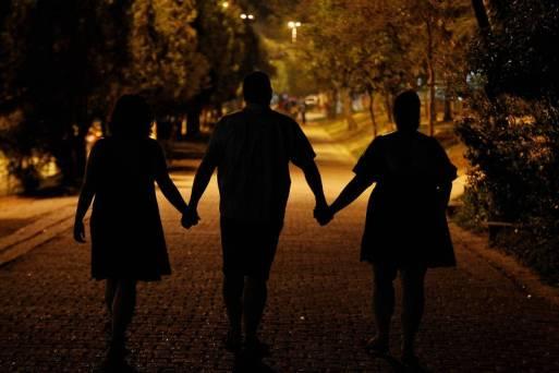 Casal formado por um homem e duas mulheres, adeptos ao poliamor