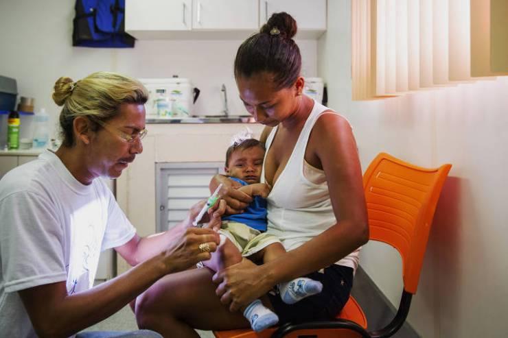 O técnico de enfermagem Mauro Coutinho aplica vacina em Rodrigo Caio Brasil, 7 meses, no colo de sua mãe Rosineti Brasil, 25, na Unidade Básica de Saúde Fluvial em Borba, no Amazonas
