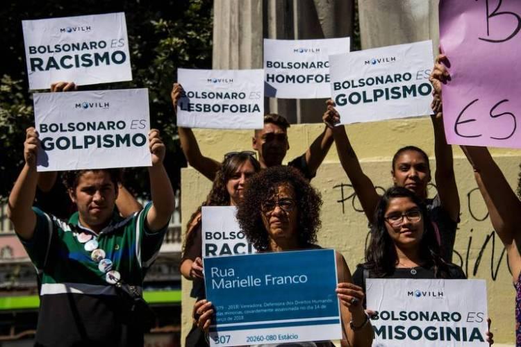 Manifestantes protestam, diante do palácio de La Moneda, contra a presença de Jair Bolsonaro no Chile