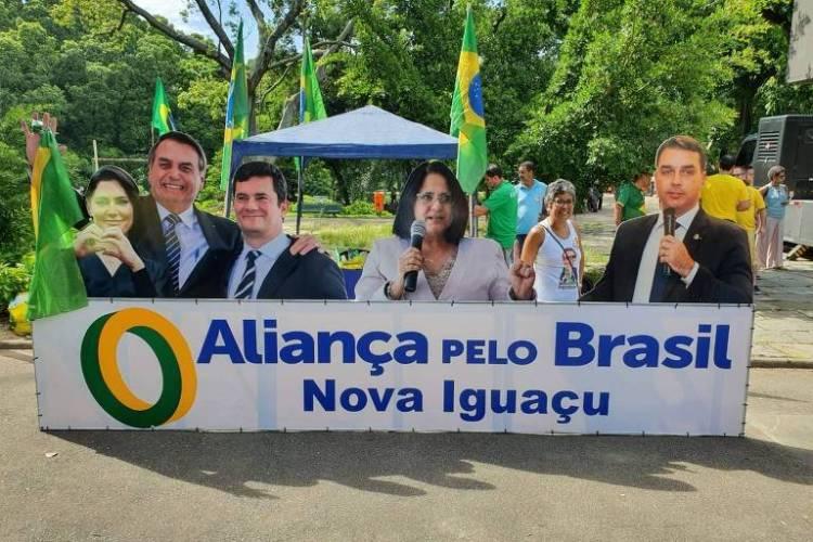 """Na placa lê-se """"Aliança pelo Brasil Nova Iguaçu"""". Da esquerda para a direita vê-se as fotos de Michelle e Jair Bolsonaro, Sergio Moro, Damares Alves e Flávio Bolsonaro"""