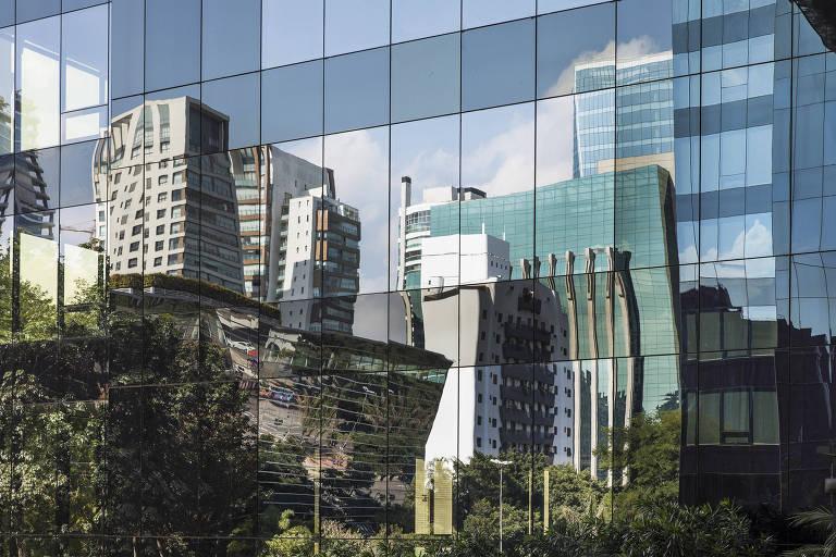 Prédios de escritórios na avenida Faria Lima refletidos na fachada de vidro do edifício Patio Victor Malzoni (onde fica o Google, entre outros)
