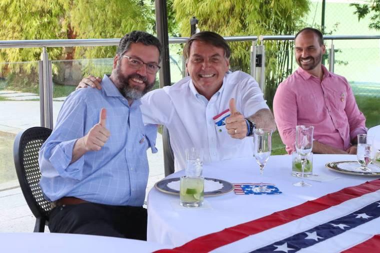 Observado pelo filho Eduardo, Bolsonaro abraça Araújo na festa da independência dos EUA, no sábado