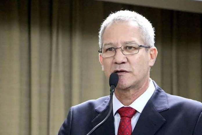 João Roberto, um homem de óculos, terno e cabelos brancos, falando ao microfone