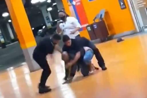 Homem sendo espancado por seguranças de um supermercado