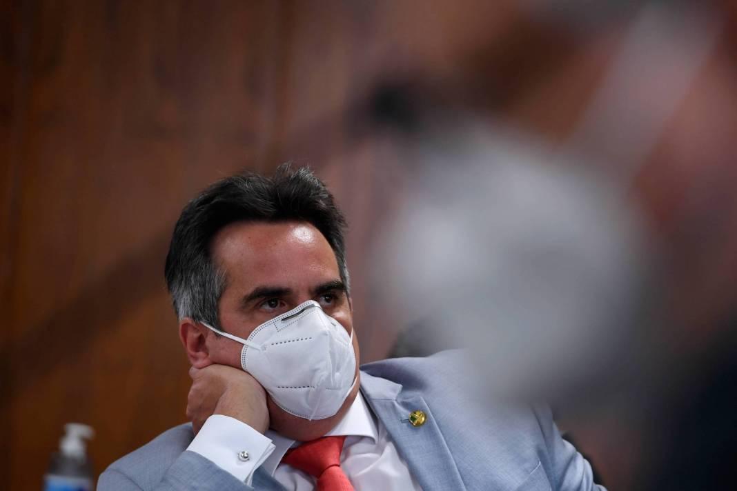 Usando uma máscara, Ciro de terno com o braço encostado à bancada e a cabeça apoiada em uma das mãos. Diante dele, uma sombra de outra pessoa de máscara