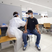 A student is given a COVID-19 vaccine at Nippon Sport Science University in Tokyo on Monday. With infections among younger people on the rise, the vaccination of that demographic will be key going forward. | KYODO