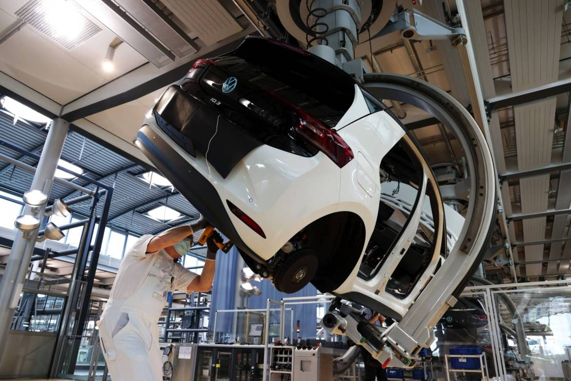 A worker secures a battery pack to a Volkswagen AG vehicle at a factory in Dresden, Germany. | BLOOMBERG