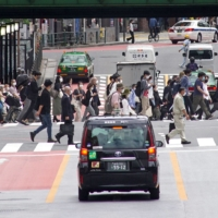 Commuters walk near JR Shinjuku Station in Tokyo. The government plans to encourage firms to let their employees choose to work four days a week instead of five, but it's unclear if the initiative will be widely accepted, with both the labor and management side voicing concerns about potential unwanted outcomes. | AFP-JIJI